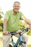 Portrait of man riding cycle in countryside Stock Photo