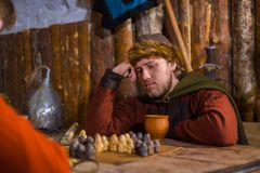 Portrait of man in russian ethnic suit playing chess Stock Images