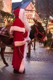 Portrait of man with santa claus costume and donkey at the christmas market royalty free stock image