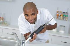 Portrait man sealing around kitchen sink. Portrait of man sealing around kitchen sink Royalty Free Stock Images