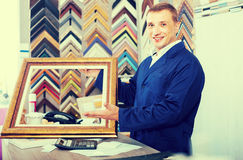 Portrait of man seller working with picture frames in atelier. Portrait of happy spanish man seller working with picture frames in atelier royalty free stock photos