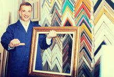 Portrait of man seller working with picture frames in atelier Royalty Free Stock Photography