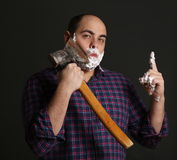 Portrait man shaving with big axe and foam on his face Royalty Free Stock Photos