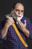 Portrait man shaving with big axe and foam on his face Royalty Free Stock Image