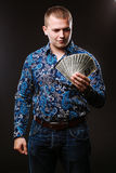 Portrait of a man in a shirt and jeans holds a lot of hundred dollar bills. The guy is holding a salary, money. Royalty Free Stock Photos