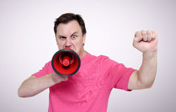 Portrait of man shouting with a red megaphone and raised fist Royalty Free Stock Image