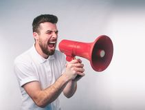 Portrait of man shouting using megaphone over background Nerd is wearing glasses. Portrait of man shouting using megaphone over green background Nerd is wearing Stock Photos