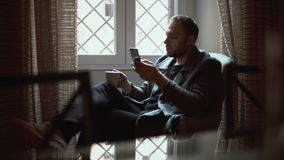 Portrait of man sitting in armchair in living room and using smartphone. Male browse the Internet and drinks coffee. stock video
