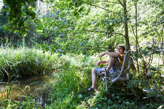 Portrait of a man. A man sitting on a bench in the forest royalty free stock images