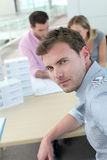Portrait of man sitting at desk with coworkers Stock Images