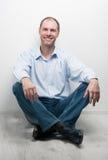 Portrait of man sitting on the floor Stock Image
