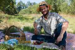 Portrait of man sitting with a glass of wine on picnic blanket Royalty Free Stock Photography