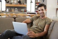 Portrait Of Man Sitting On Lounge Sofa Using Laptop Royalty Free Stock Images