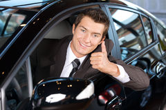 Portrait of man sitting in new car showing thumbs up Royalty Free Stock Photography