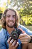 Portrait of man sitting in park with digital camera Royalty Free Stock Photo