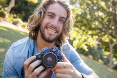 Portrait of man sitting in park with digital camera Royalty Free Stock Images