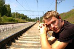 Portrait of the man sitting on the railway in a br Stock Images