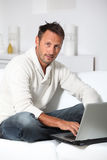 Portrait of man sitting in sofa with laptop Stock Photography