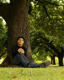 Portrait Of Man Sitting By Tree 2 Royalty Free Stock Photos