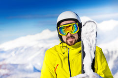 Portrait of man with ski over mountains. Portrait of skier man standing with ski and mask with helmet wearing beard over the peaks of mountains Stock Photography