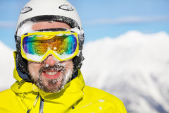Portrait of man skier with snow on face. Close portrait of a man wearing beard ski mask and helmet with snow on face and mountain on background Royalty Free Stock Photography