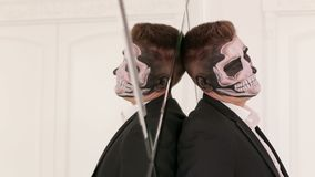 Portrait of a man with a skull makeup he leaned against the mirrored wall. Close-up portrait of a man with a skull makeup dressed in a tail-coat, against the stock video