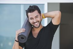 Portrait of a man smiling holding yoga mat. Portrait of a man holding yoga mat and smiling with his hand behind his head Stock Photography