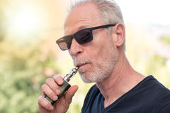 Portrait of man smoking an electronic cigarette, light effect. Portrait of mature man smoking an electronic cigarette, light effect Royalty Free Stock Images