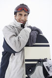 Portrait Of Man With Snowboard Against Sky Stock Photos