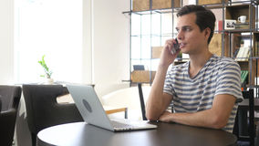 Portrait of man speaking on mobile phone, sitting at desk Stock Images