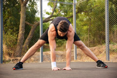 Portrait of a man in sportswear stretching legs outdoors. Portrait of a bearded young man in sportswear stretching legs outdoors Stock Images