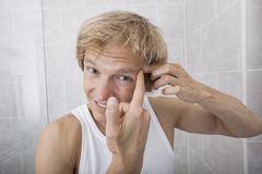 Portrait of man squeezing pimple on his forehead in bathroom Royalty Free Stock Images