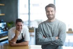 Portrait of man standing with arms crossed at counter Stock Photos