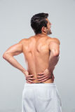 Portrait of a man standing with back pain Stock Image