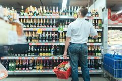 Portrait of a man standing on the background of alcoholic beverages of the supermarket. Stock Photo