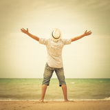 Portrait of  man standing on the beach at the day time. And raising hands Royalty Free Stock Images