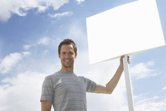 Portrait of man with standing by blank sign against cloudy sky Stock Photography