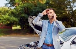 Man standing at a broken car and calling royalty free stock photos