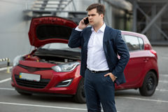 Portrait of man standing at broken car and calling repair servic Stock Images