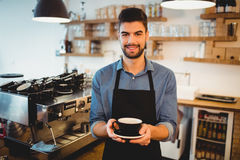 Portrait of man standing with a cup of coffee in office cafeteria. Portrait of smiling man standing with a cup of coffee in office cafeteria Stock Photography