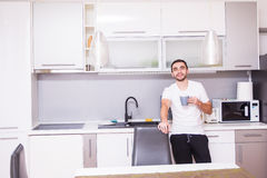 Portrait of man standing in kitchen holding a cup of coffee looking away in thought. Relaxed young man having coffee at home in ki royalty free stock photos