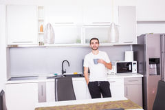 Portrait of man standing in kitchen holding a cup of coffee looking away in thought. Relaxed young man having coffee at home in ki Stock Photos