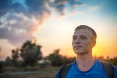 Portrait of a man with standing outdoors in the evening. Contemplates amazing view of beautiful sunset sky stock images