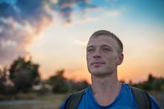Portrait of a man with standing outdoors in the evening. Contemplates amazing view of beautiful sunset sky royalty free stock images