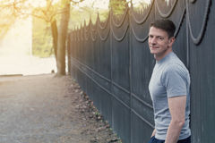 Portrait of man standing outdoors next to a fence Royalty Free Stock Image