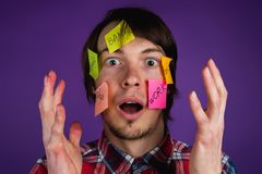 Portrait of a man with stickers on his face shocked by obligations, a man with his hands up in the face in shock from. Everyday routine, purple background Royalty Free Stock Photos