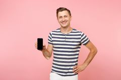 Portrait of man in striped t-shirt showing mobile phone camera with blank black empty screen copy space isolated on. Trending pastel pink background. People stock photography