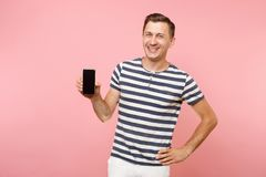 Portrait of man in striped t-shirt showing mobile phone camera with blank black empty screen copy space isolated on. Trending pastel pink background. People stock photo