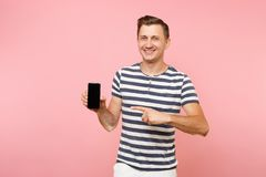 Portrait of man in striped t-shirt showing mobile phone camera with blank black empty screen copy space isolated on. Trending pastel pink background. People stock images