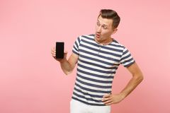 Portrait of man in striped t-shirt showing mobile phone camera with blank black empty screen copy space isolated on. Trending pastel pink background. People royalty free stock images